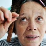 Senior female tweezing eyebrow — Stock Photo