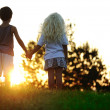 Happy children in nature at sunset - Stok fotoraf