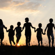 Children running on meadow at sunset time — Stockfoto