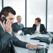 Business man speaking on the phone while in a meeting — Stockfoto