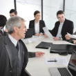 Stock Photo: Senior businessman at a meeting. Group of colleagues in the background