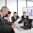 CEO reading report at business meeting — Stock Photo #10421986