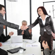 Business partners shaking hands after making deal while their co-workers applauding — Foto Stock