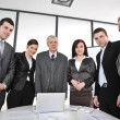 Foto de Stock  : Multi aged business standing around the table at office