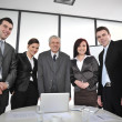 Multi aged business standing around the table at office — Stockfoto