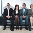 Four business sitting in a row on sofa — Stok fotoğraf