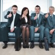 Group of business sitting on sofa with thumbs up - Stock Photo