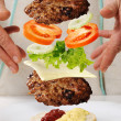 Levitating zero gravity burger in hands - Stock Photo