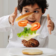 Little boy with hamburger ingredients in hands — Stock Photo