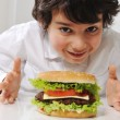 Cute little boy with burger — Stock Photo