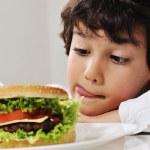 Boy on temptation with burger — Stock Photo