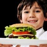 Little boy offering a hamburger on plate — Stock Photo