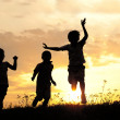 Stock Photo: Children running on meadow at sunset