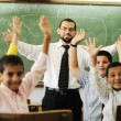 Teacher with boys and girls in school — Stock Photo