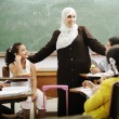 Muslim arabic children with teacher at school — Stock Photo