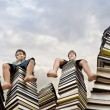 Stock Photo: Little boy sitting on large stack of books