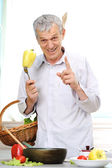 Good looking elderly man working in kitchen — Stock Photo