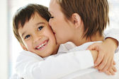 Happy mother embracing and kissing her son — Stock Photo
