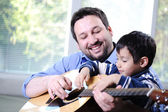 Father and son playing guitar at home — Stock Photo