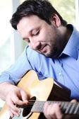 Homme jouant de la guitare et se détendre à la maison — Photo