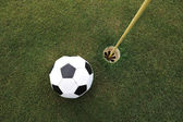 Football big ball at golf field hole — Stock Photo