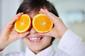 Little boy holding orange slices on eyes as sunglasses — Stock Photo