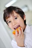 Child eating fresh orange fruit — Foto de Stock