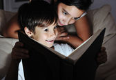 Boy and girl reading light book at night, children concept — Stock Photo