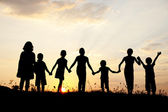 Group of children playing at summer sunset — Stock Photo