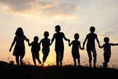 Children running on meadow at sunset time — Stok fotoğraf