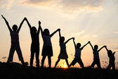 Several children generations with arms up in nature — Stock Photo