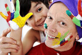 Grandmother playing with messy grandson — Stock Photo