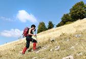 Caminar a cuesta arriba mujer trekking y senderismo montañismo — Foto de Stock
