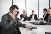Business man speaking on the phone and typing on laptop while in a meeting — Stock Photo