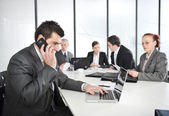 Businessman calling on phone, business meeting at background — Stock Photo