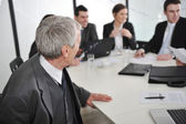 Senior male speaking at a business meeting at office — Stock Photo
