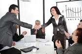 Business partners shaking hands after making deal while their co-workers applauding — Stock Photo