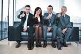 Group of business sitting on sofa with thumbs up — Stock Photo