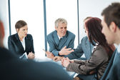 Portrait of a positive manager with his team sitting at the table — Stock Photo
