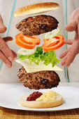 Levitating zero gravity burger in hands — Stock Photo
