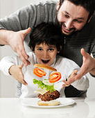 Kid and father making burger together — Stock Photo