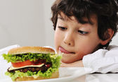 Boy on temptation with burger — Stock Photo