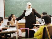 Muslim arabic children with teacher at school — Stock Photo