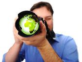 Man with camera earth green lens — Stock Photo