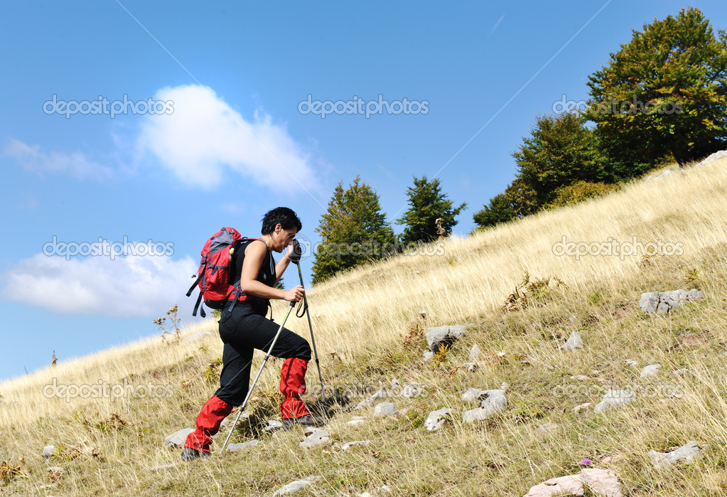 Walking uphill woman trekking and hiking mountaineering — Stock Photo #10421672