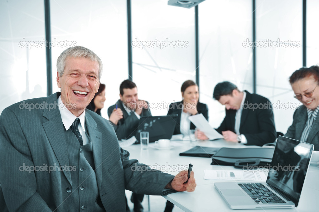 Senior businessman at a meeting. Group of colleagues in the background — Foto Stock #10421981