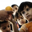 Refugee camp, poverty, hungry children receiving humanitarian food - Stok fotoğraf