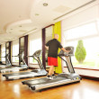 Stock Photo: Young athletic man running on a treadmill at the modern bright gym