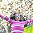 Stock Photo: Pretty little girl in establishment of branches of blossoming apple