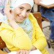 Cute Muslim arabic girl sitting on the chair and holding pencil - at school — Stock Photo #8843823